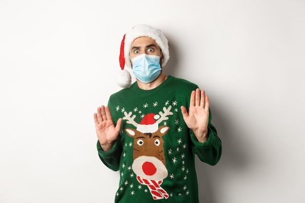 Concepto de covid-19 y vacaciones navideñas. chico ansioso y asustado con sombrero de santa con máscara médica rechazando algo, rechazando la oferta, de pie sobre fondo blanco.