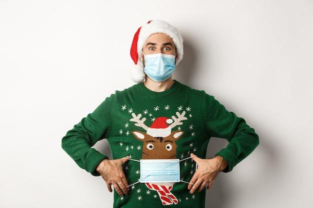 Concepto de covid-19 y vacaciones navideñas. chico divertido poner mascarilla en su suéter ciervo, de pie sobre fondo blanco.