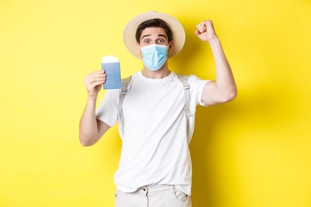 Concepto de covid-19, viaje y cuarentena. turista de hombre feliz con máscara médica celebrando, mostrando el pasaporte con boletos para vacaciones y regocijo, viaje durante el coronavirus.