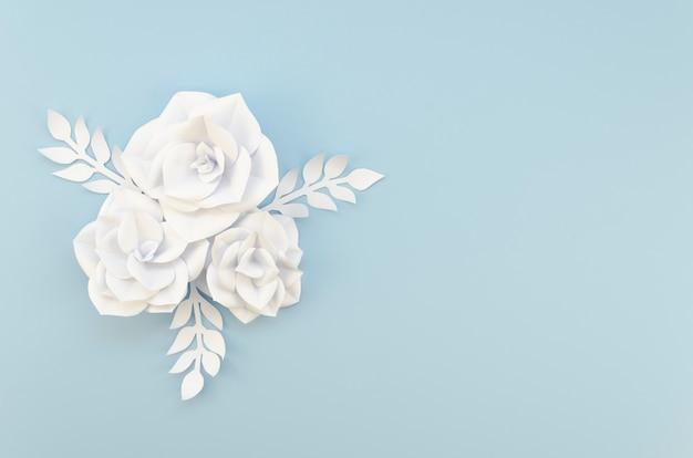 Concepto de creatividad con flores blancas sobre fondo azul.
