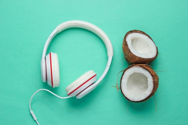 Concepto creativo de amante de la música. fondo de verano. auriculares clásicos blancos, mitades de coco sobre fondo azul.