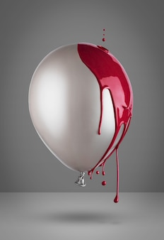 Concepto creativo de globo gris cubierto de goteo de pintura roja. mínimo.