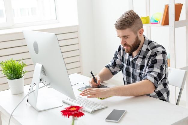 Concepto creativo, ilustrador, gráfico y de personas: hombre de negocios masculino creativo que escribe o dibuja en una tableta gráfica mientras usa una computadora portátil en la oficina