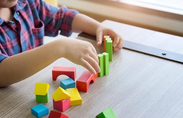 Concepto creativo; el niño juega coloridos bloques de madera en casa.
