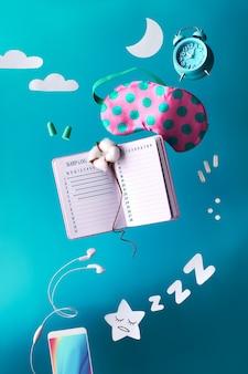 Concepto creativo de sueño nocturno saludable con diario manuscrito de registro de sueño. máscara para dormir voladora o levitante, despertador, auriculares, tapones para los oídos, píldoras.