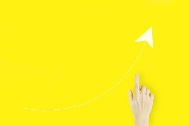 Concepto de crecimiento. dedo acusador de la mano de la mujer joven con la flecha blanca del holograma en fondo amarillo. estrategia de negocios. publicidad digital.