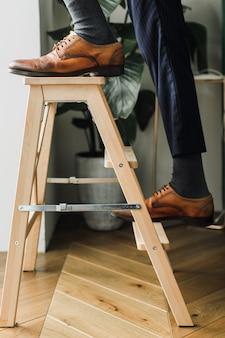 El concepto de crecimiento profesional de los pies del hombre sube las escaleras