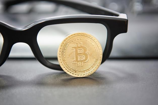 Concepto de criptomoneda bitcoin. gafas y teclado de escritorio en el fondo. ocupación bursátil e intercambio