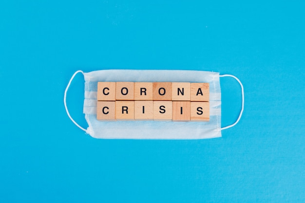 Concepto de crisis de coronavirus con máscara médica, cubos de madera en la mesa azul plana.
