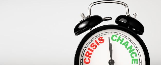 Concepto de crisis y oportunidad en concepto de reloj despertador negro.