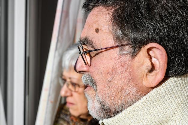 Concepto de cuarentena de coronavirus y distanciamiento social. senior pareja, en casa mirando por la ventana con expresión preocupada. quedarse en casa. estilo de vida mayor y jubilado.