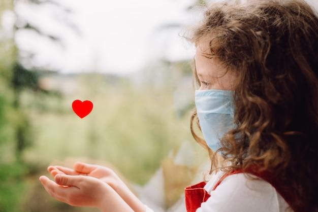 Concepto de cuarentena de coronavirus. niño pequeño con mascarilla protectora médica para proteger la salud del virus de la gripe, sentado en el alféizar de la ventana con el corazón rojo. covid-19 autoaislamiento en el hogar