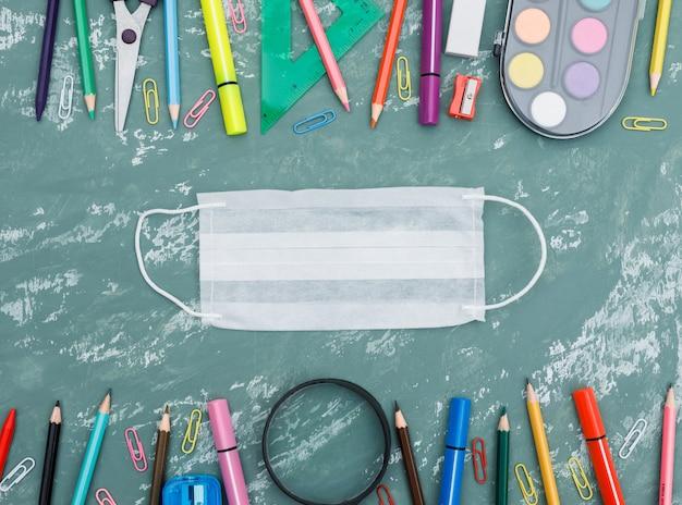 Concepto de cuarentena escolar con máscara médica, lupa, útiles escolares sobre fondo plano de yeso.