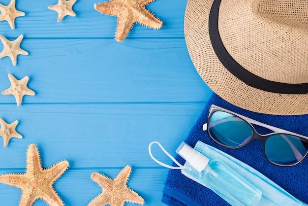 Concepto de cuarentena de vacaciones y covid. arriba, vista aérea, primer plano, foto, de, toalla, gafas de sol, estrella de mar, desinfectante, máscara, y, sombrero, aislado, en, azul, madera, plano de fondo, con, copyspace