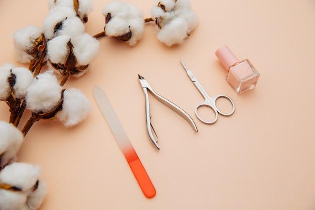 Concepto de cuidado de la belleza. un conjunto de herramientas profesionales para manicura y pedicura en superficie rosa.