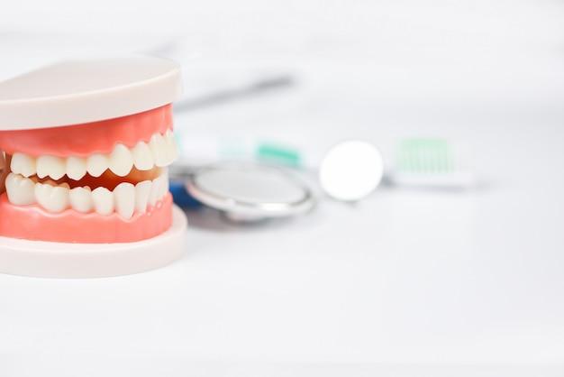 Concepto de cuidado dental: herramientas de dentista con prótesis dentales, instrumentos de odontología e higiene dental y chequeo de equipos con modelo de dientes y espejo bucal de salud bucal