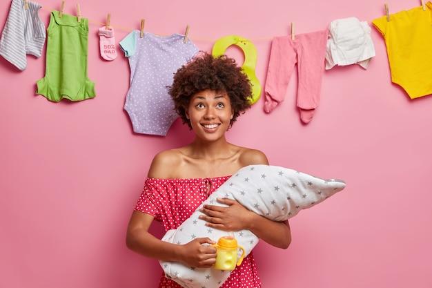 Concepto de cuidado infantil, paternidad feliz, familia y amor. la mujer sonriente positiva posa con el recién nacido somnoliento después de la alimentación, sostiene el biberón de leche, disfruta de la maternidad, se para en el interior. bebé en manos de las madres