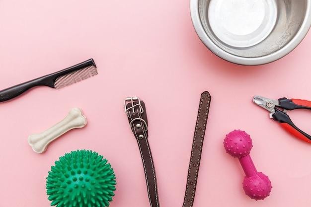 Concepto de cuidado de mascotas y animales. juguetes y accesorios para jugar y entrenar perros aislados sobre fondo de moda rosa pastel