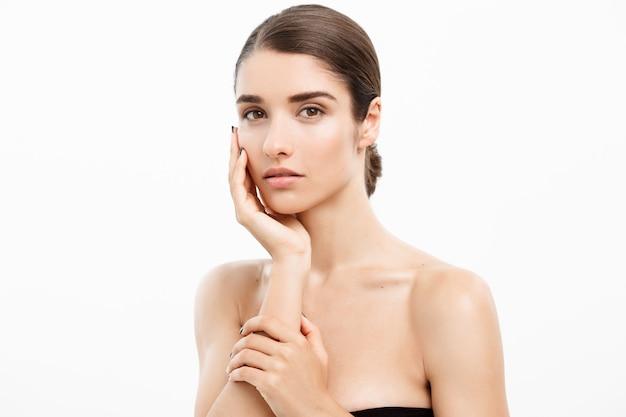 Concepto de cuidado de la piel de belleza. mujer caucásica tocándola aislado en blanco