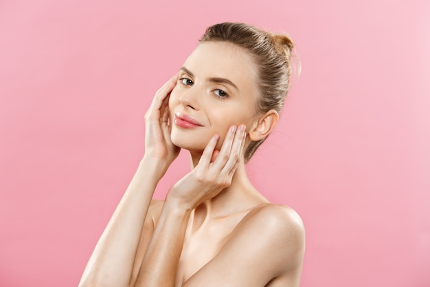 Concepto de cuidado de la piel - encantadora mujer caucásica joven con maquillaje perfecto composición de fotos de niña morena. aislado en fondo de color rosa con espacio de copia.