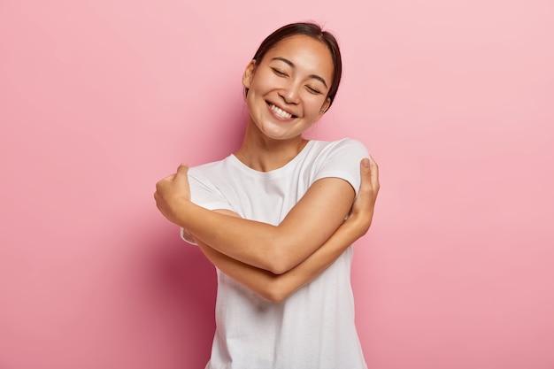 Concepto de cuidado y ternura. alegre mujer asiática morena positiva se abraza suavemente, inclina la cabeza y sonríe feliz, mantiene los ojos cerrados por el placer, tiene un estado de ánimo romántico, vestida con ropa informal