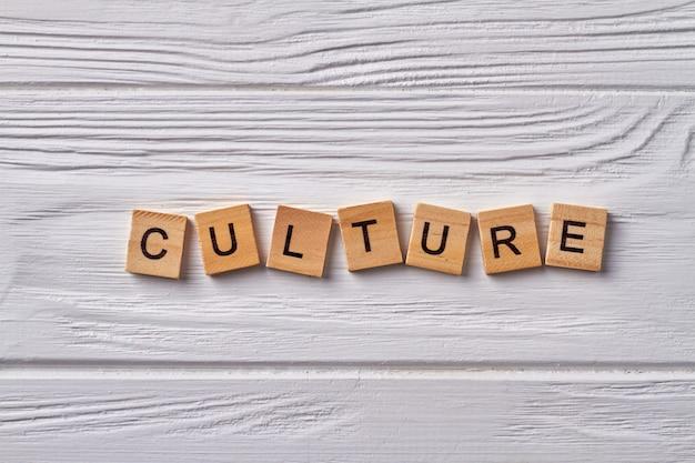 Concepto de cultura y civilización. logros de una nación en particular u otro grupo social. letras en cubos del alfabeto aislados sobre fondo de madera.