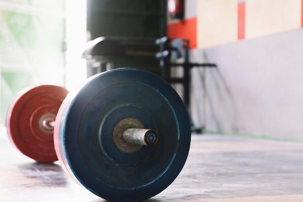 Concepto de culturismo con barra de pesas en gimnasio
