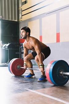 Concepto de culturismo con hombre entrenando con barra de pesas