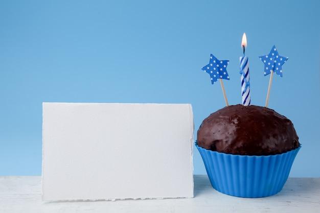 Concepto de cumpleaños con cupcake y vela junto a la tarjeta de felicitación vacía sobre fondo azul.