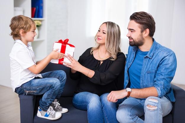 Concepto de cumpleaños o navidad - pareja joven dando regalo a hijo pequeño
