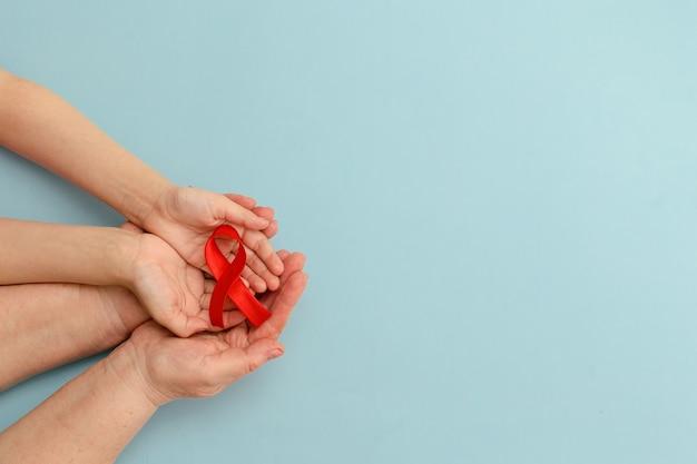 Concepto de dar transfusión de sangre las manos de la madre y el niño sostienen la cinta roja día de la hemofilia