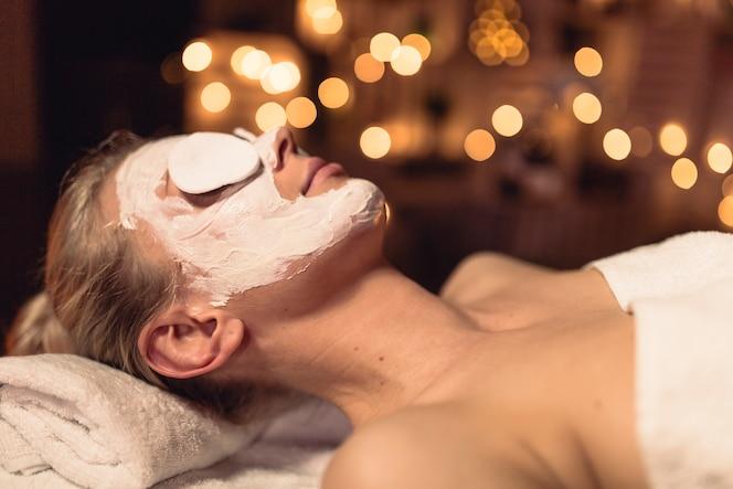 Concepto de bienestar con mujer con crema en la cara