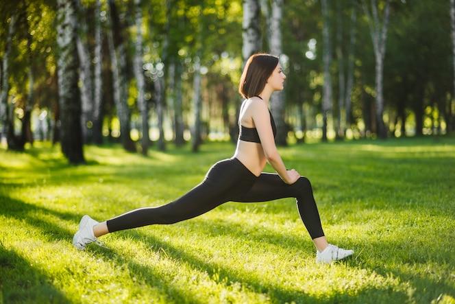 Concepto de fitness, deporte, entrenamiento, parque y estilo de vida - chica haciendo ejercicios al aire libre