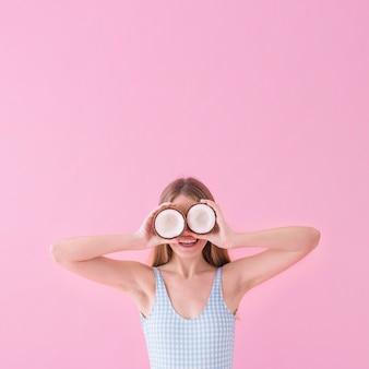 Concepto de moda de verano con mujer sujetando coco enfrente de los ojos