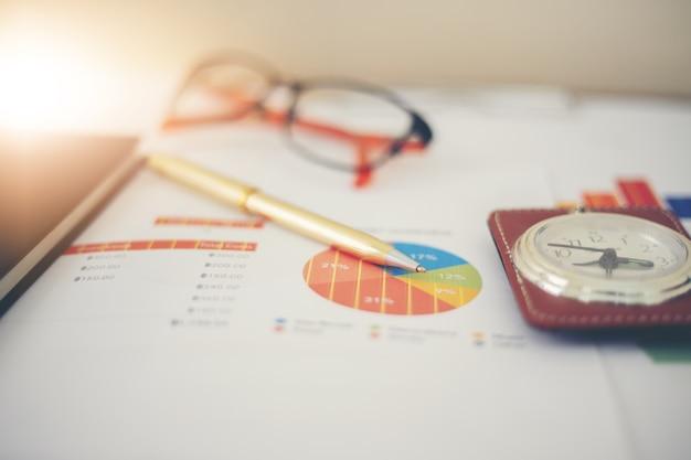Concepto de negocio de trabajo de oficina y gráficos de análisis y reloj en la mesa