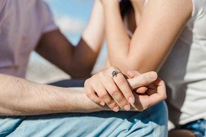 Concepto de pareja y verano con manos de cerca