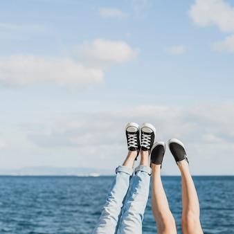 Concepto de pareja y verano con piernas enfrente del mar