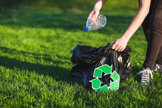 Concepto de reciclaje con mujer recogiendo basura