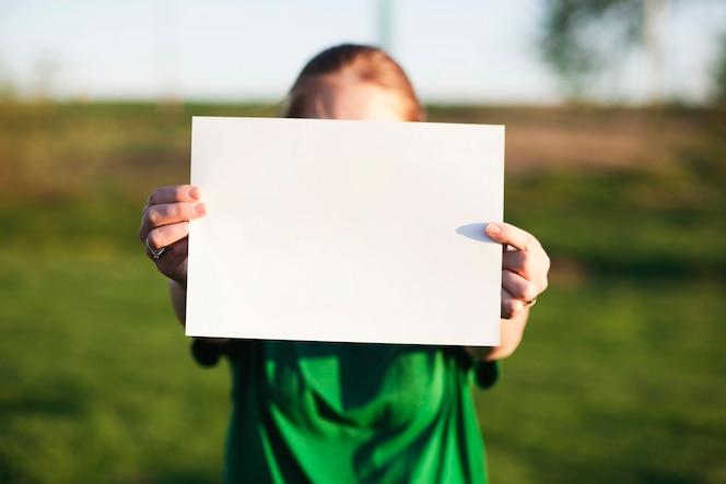 Concepto de reciclaje con mujer sujetando papel en blanco