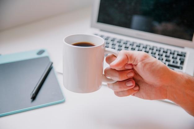 Concepto de tecnología y escritorio con mano sujetando taza