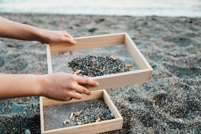 Concepto de voluntario y playa con cigarros