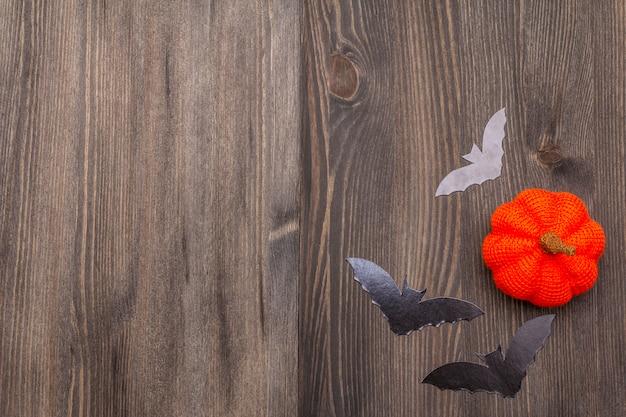 Concepto de decoración de halloween - murciélagos negros y calabaza naranja sobre fondo de madera oscura