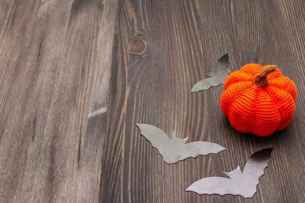 Concepto de decoración de halloween - murciélagos negros y naranja calabaza en mesa de madera oscura