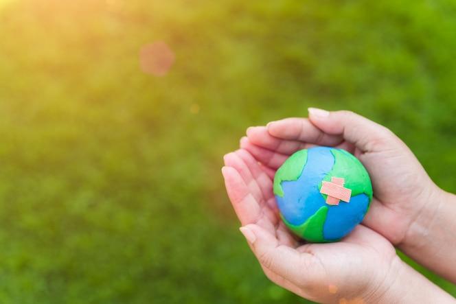 Concepto del día de la tierra mano de la mujer que sostiene el globo hecho a mano en fondo de la hierba verde.