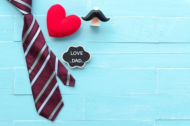 Concepto del día de padres. lazo rojo, corazón rojo, bigote con el texto del amor del papá en fondo azul.