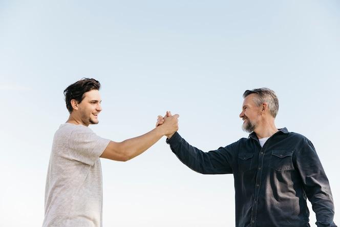 Concepto del día del padre con hijo y padre chocando manos