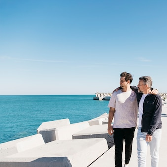 Concepto del día del padre con padre e hijo andando al lado del mar
