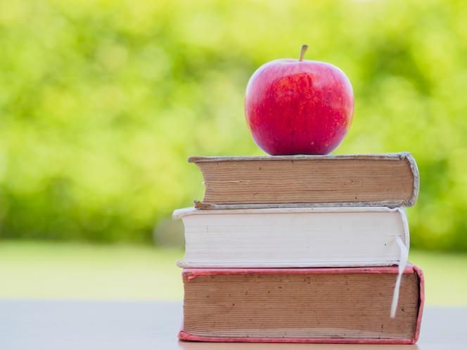 Concepto del día mundial del libro manzana roja poner en la pila de libros antiguos