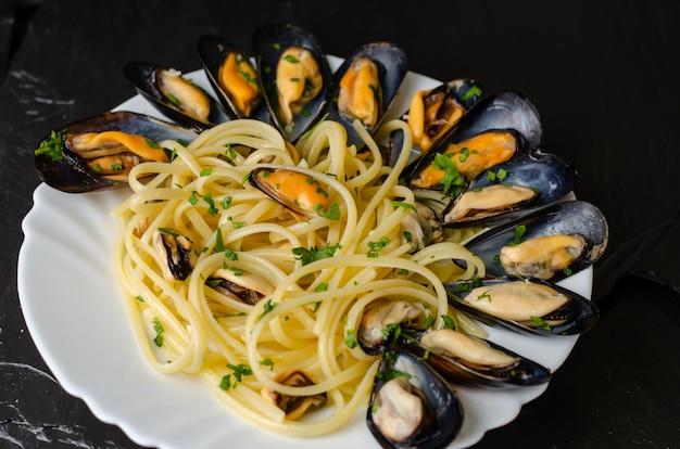 Concepto de delicadeza italiana mariscos. pasta con mejillones y perejil