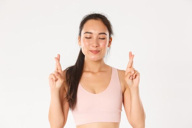 Concepto de deporte, bienestar y estilo de vida activo. primer plano de una niña asiática optimista sonriente, esperanza de perder peso, cruzar los dedos para la buena suerte y cerrar los ojos mientras pide deseos, pared blanca
